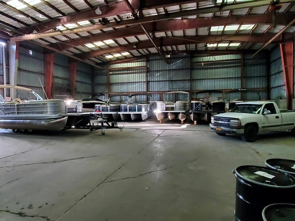 A row of sweetwater pontoon boats on blocks for the winter inside our storage building
