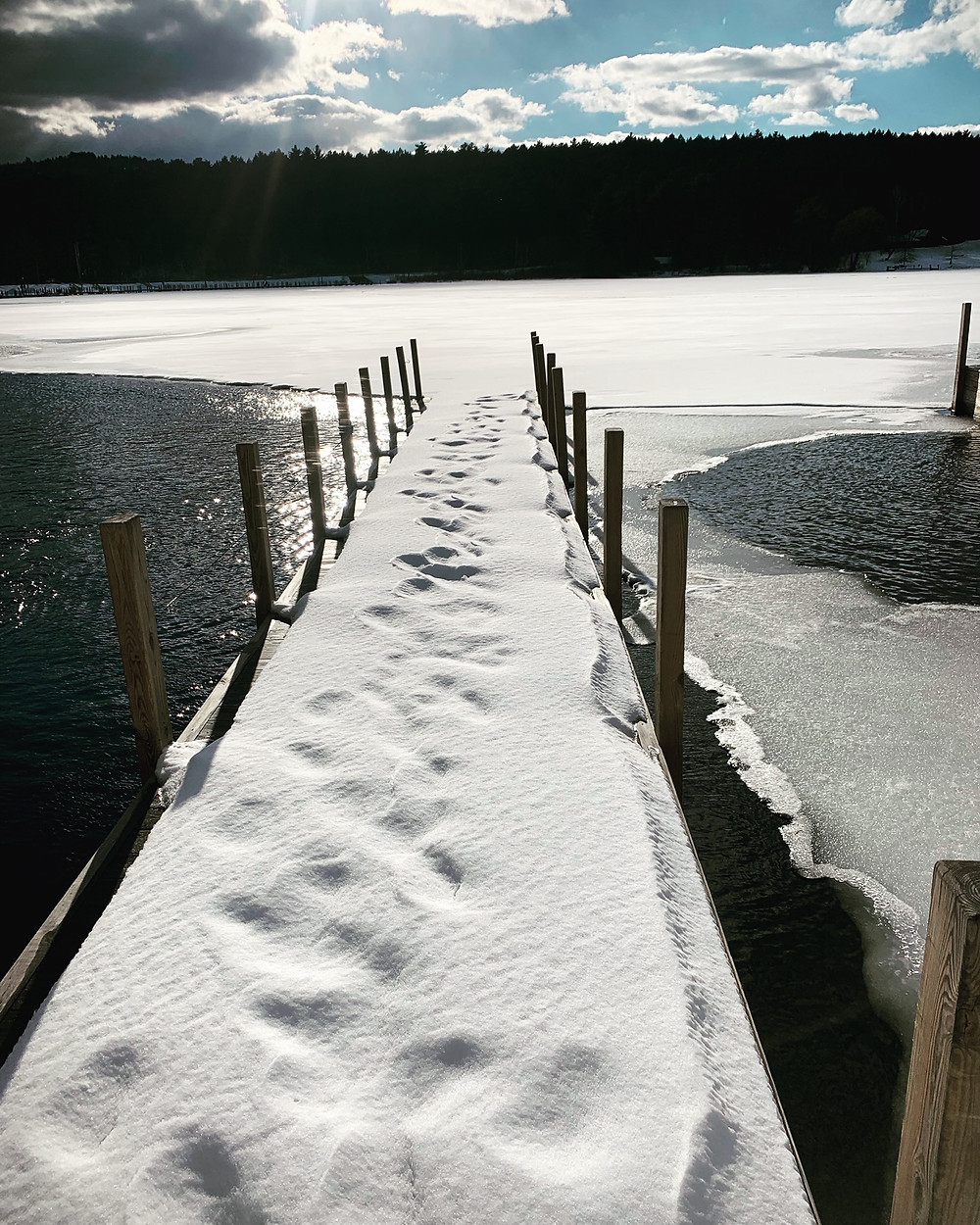 Snow covered dock at Queen Boat Co with open water starting to surround the dock as the ice begins to melt