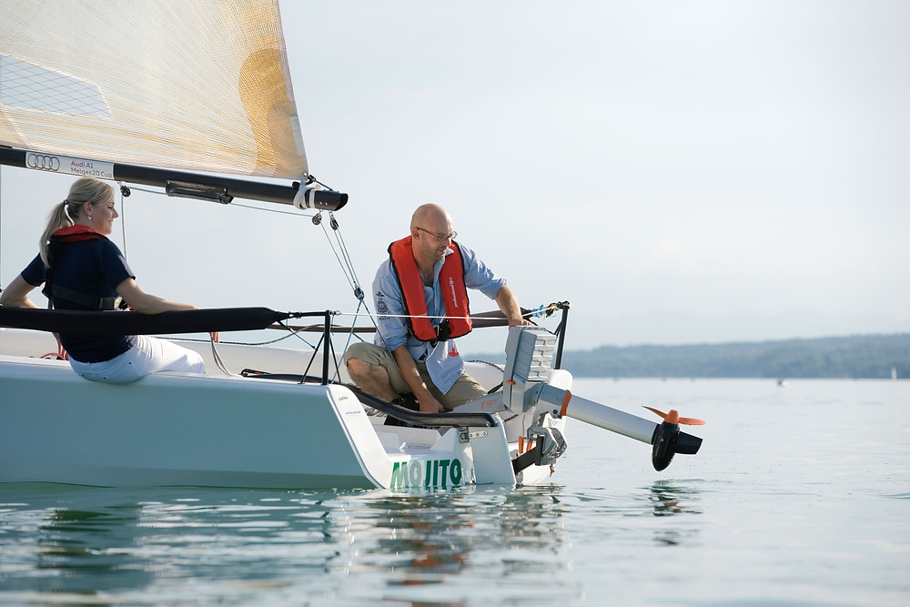 A Torqeedo electric motor mounted on a sailboat and lifted out of the water