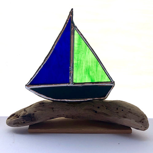 Stained glass boat set on a natural driftwood base