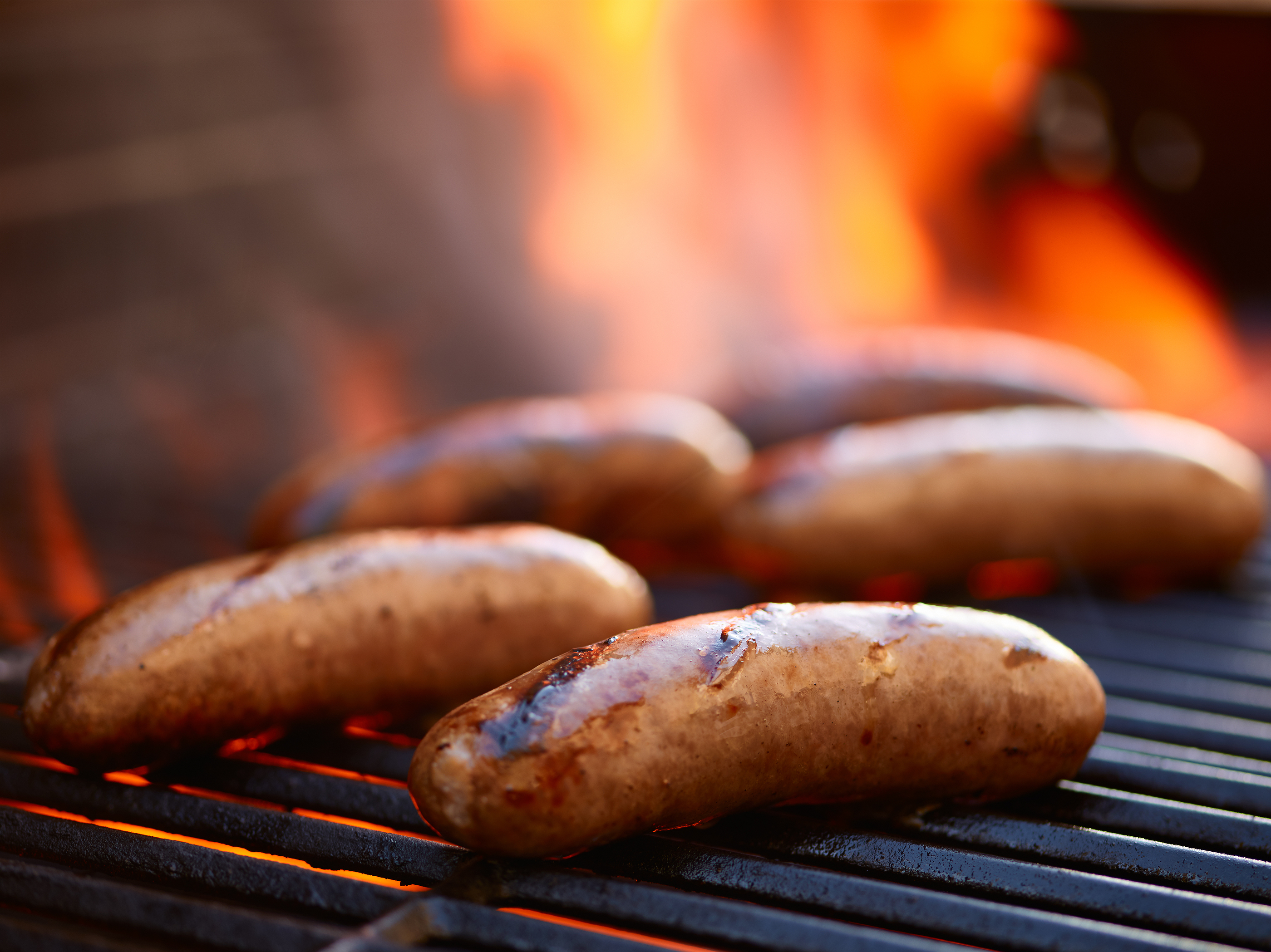 grilling bratwurst sausages over flaming grill