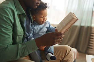 father-reading-book-to-baby-VLE6H6N.jpg