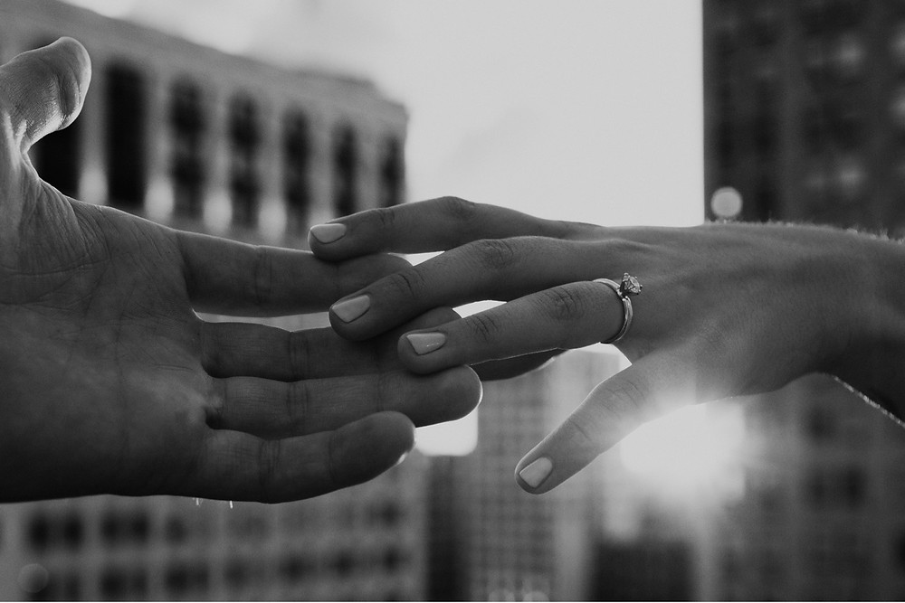 Engagement ring in the sunlight holding hands. Photographed by Nicole Leanne Photography.