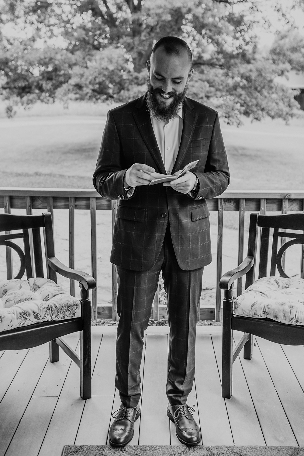 Black and white photo of groom reading letter written by bride. Photographed by Nicole Leanne Photography.