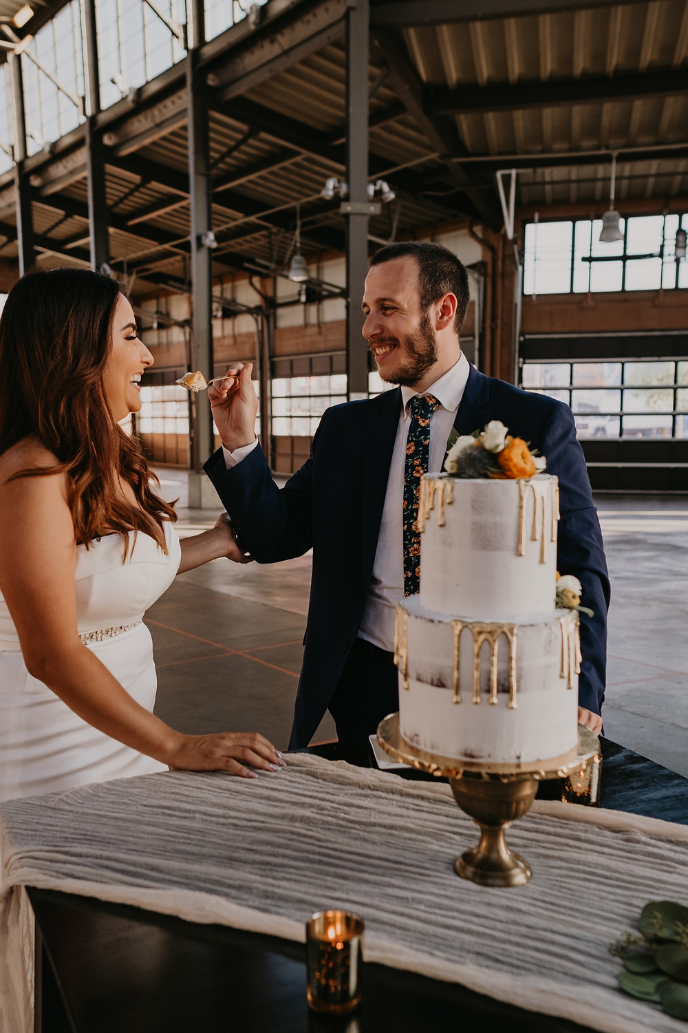 Bride and groom sharing cake at Eastern Market industrial style wedding. Photographed by Nicole Leanne Photography.