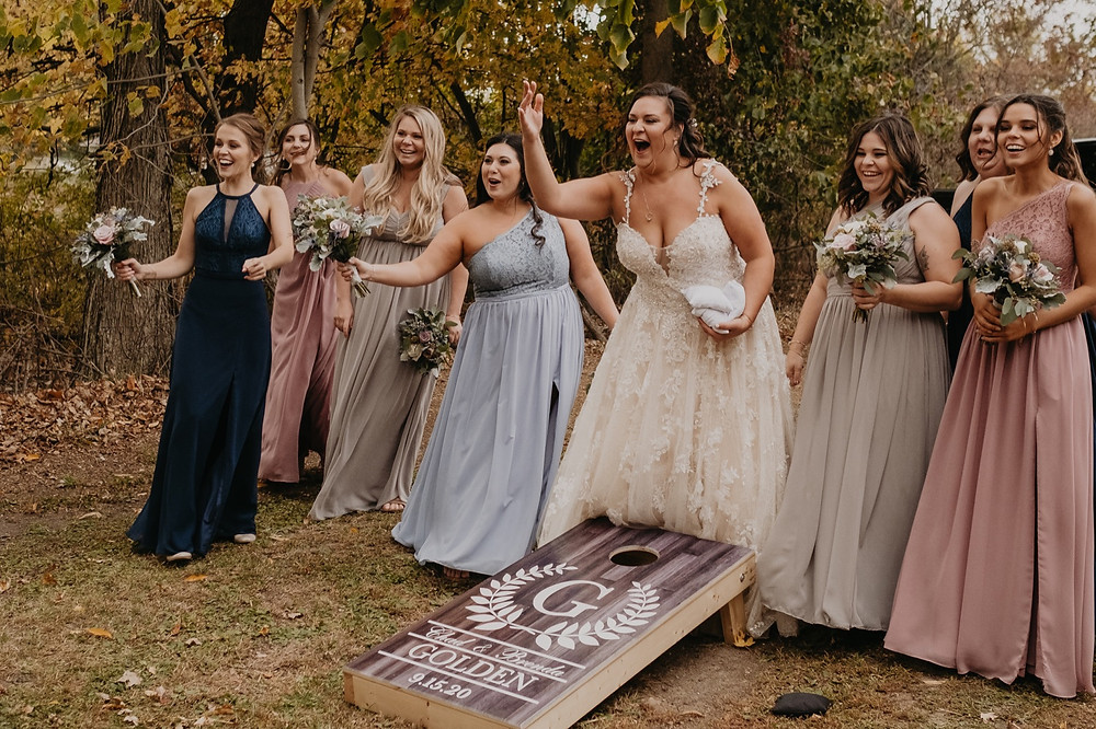 Bride playing corn hole at wedding with guests