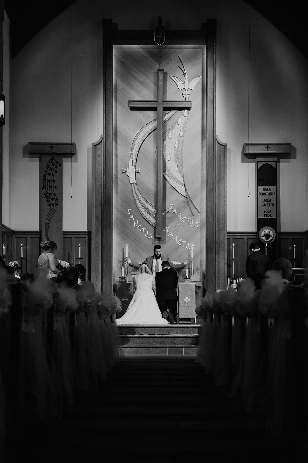 Bride and groom kneeling at altar during traditional Catholic wedding ceremony. Photographed by Nicole Leanne Photography.