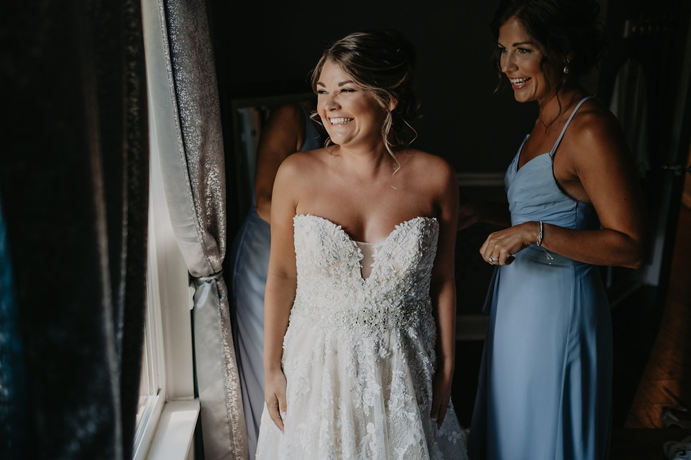 Bride with bridesmaids putting on wedding dress. Photographed by Nicole Leanne Photography.