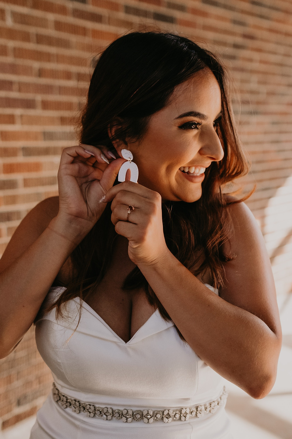 Bride with earrings ready for wedding. Photographed by Nicole Leanne Photography.