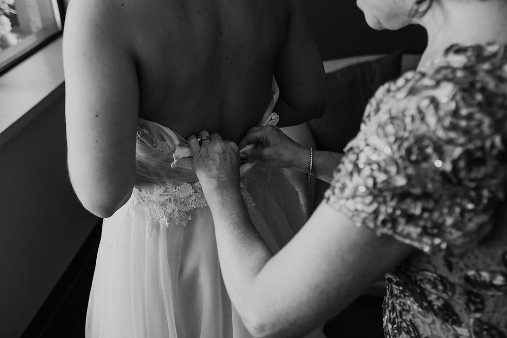 Bride getting in to wedding dress on wedding day. Photographed by Nicole Leanne Photography.