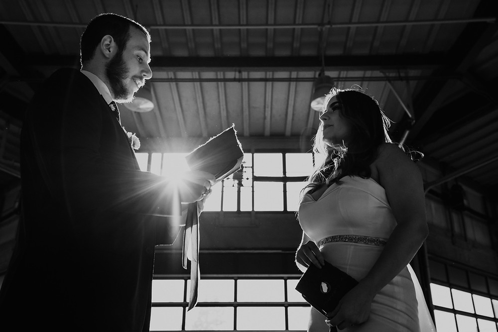 Black and white photo of bride and groom exchanging vows at Eastern Market. Photographed by Nicole Leanne Photography.