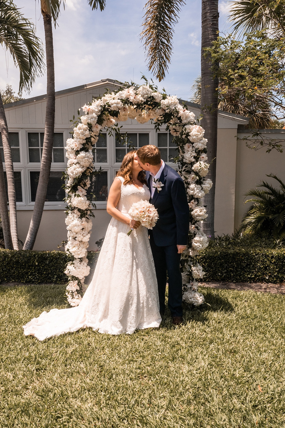 Bride and groom kiss as newlywed couple under arch of flowers