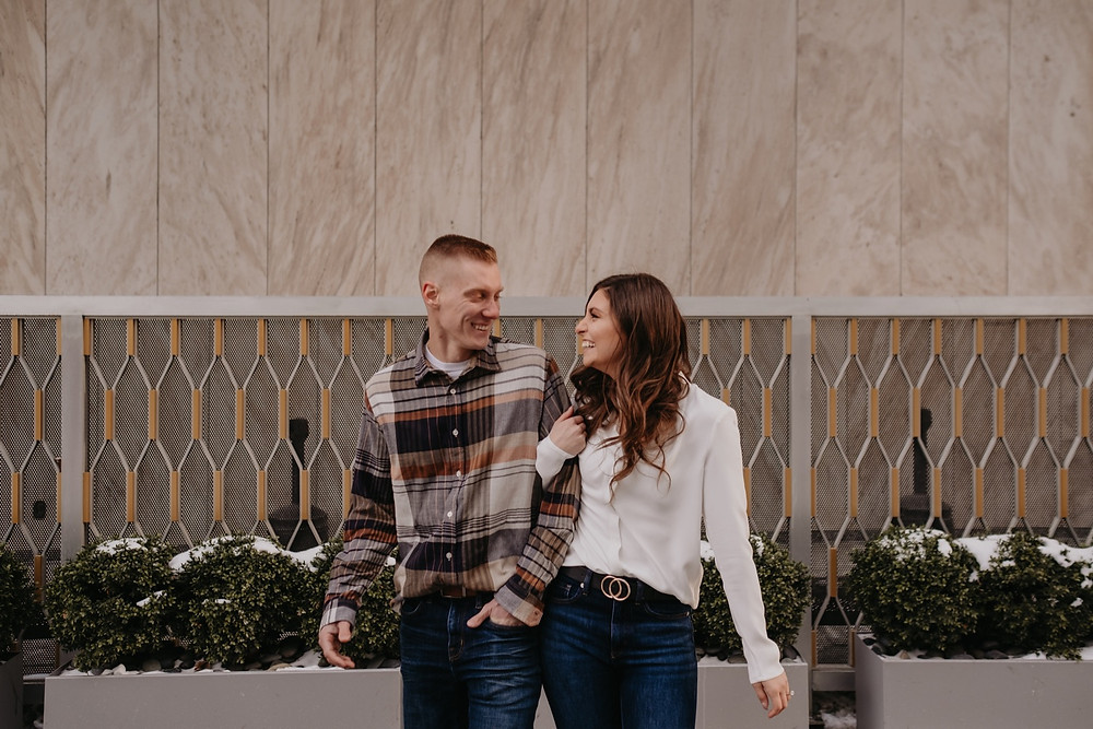 Couple laughing during Downtown Detroit engagement session. Photographed by Nicole Leanne Photography.