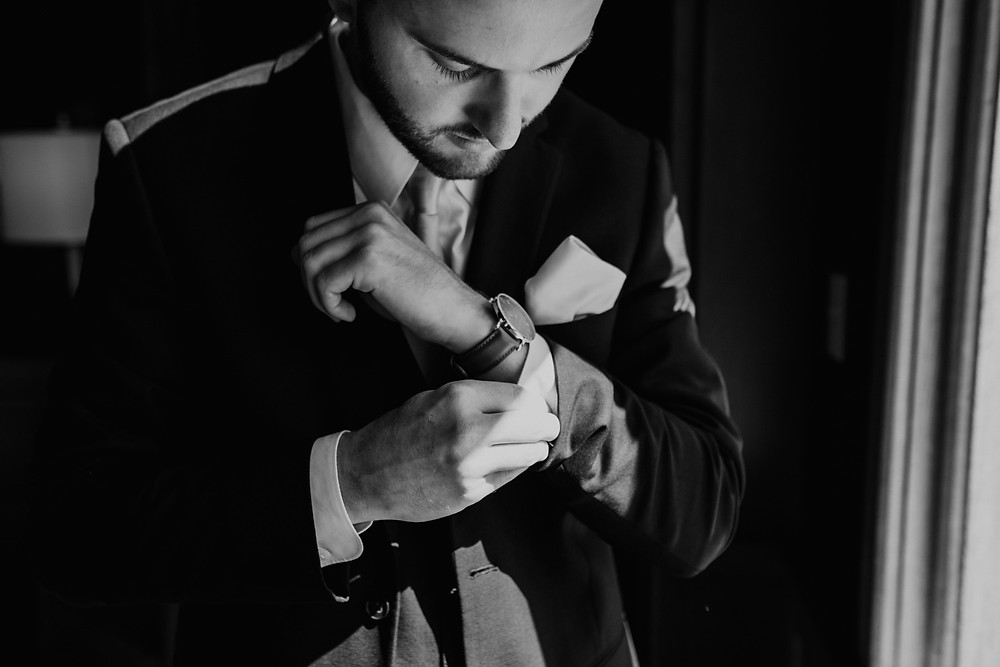 Groom getting dressed for wedding at Mission Point Resort. Photographed by Nicole Leanne Photography.