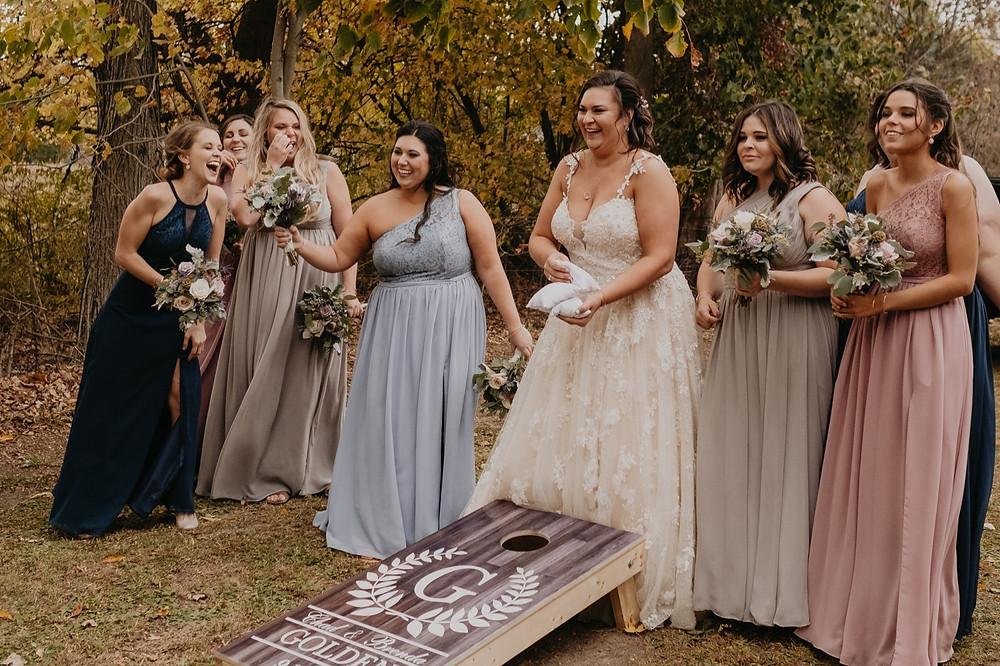 Bride and bridesmaids playing cornhole at wedding