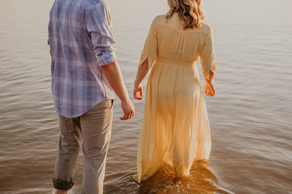 Couple wading in water at Stony Creek Metro Park. Photographed by Nicole Leanne Photography