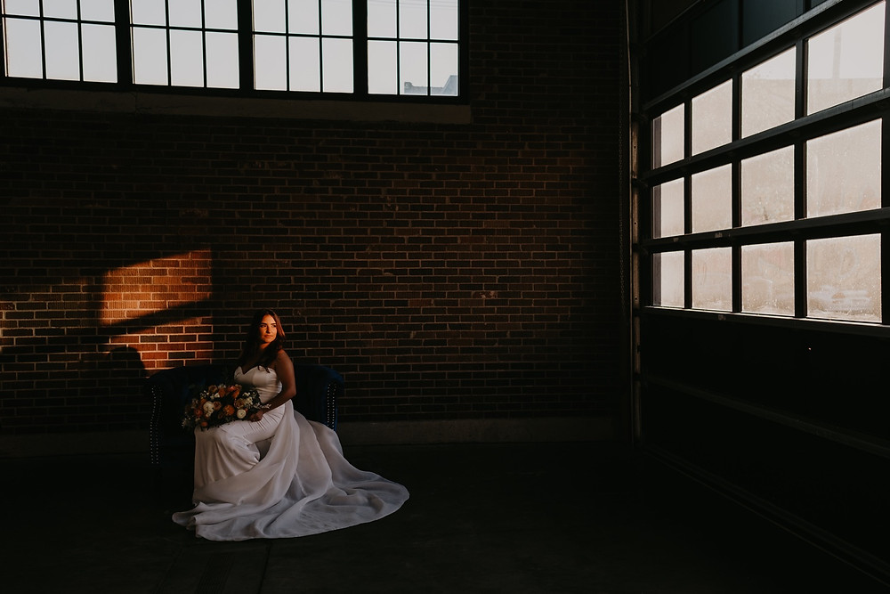 Bride looking out Eastern Market door at sunset with bouquet of flowers. Photographed by Nicole Leanne Photography.