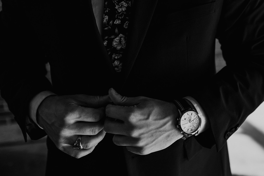 Black and white photo of groom wearing watch buttoning jacket. Photographed by Nicole Leanne Photography.