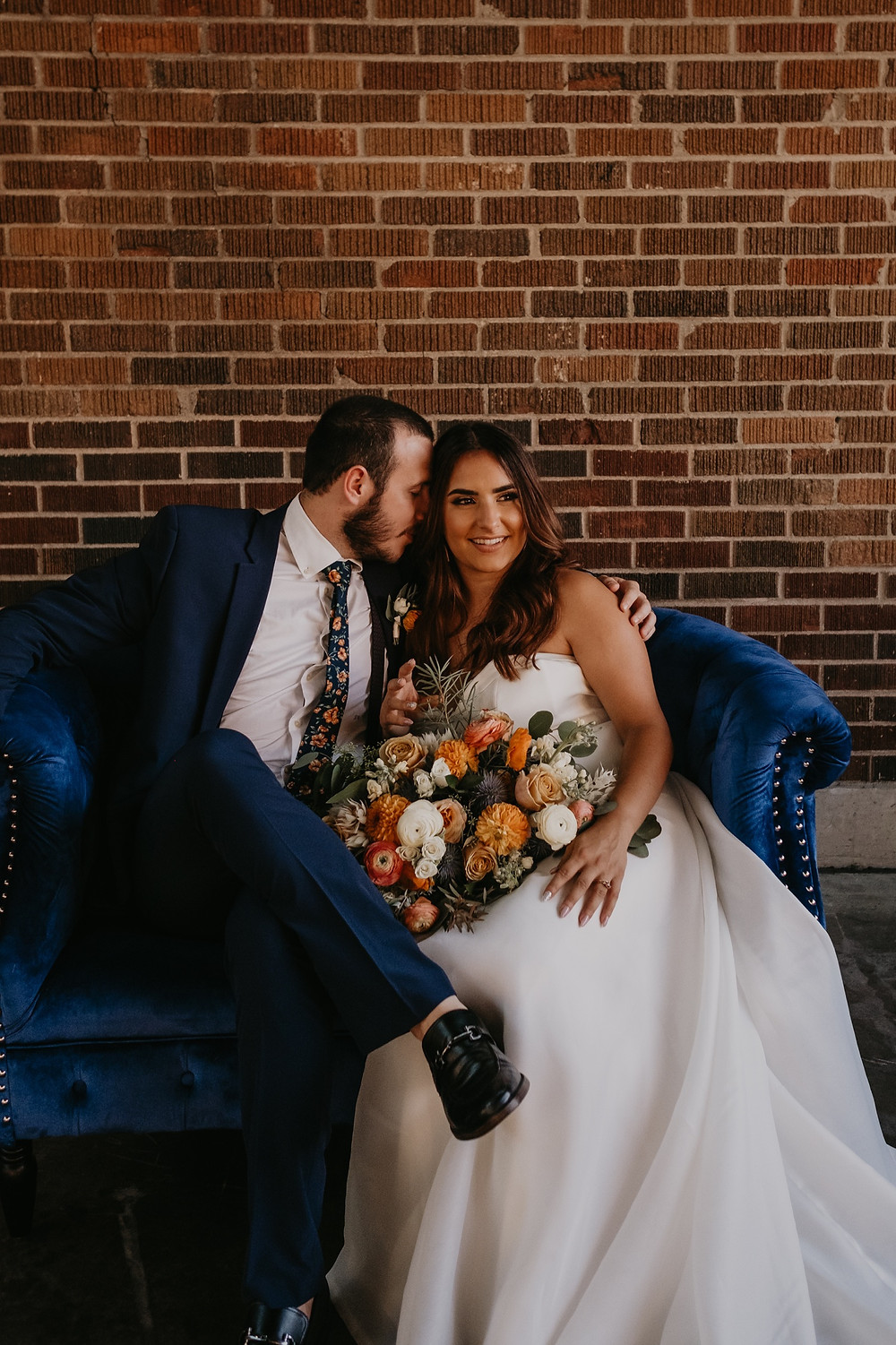 Bride and groom on blue velvet couch at Eastern Market. Photographed by Nicole Leanne Photography.