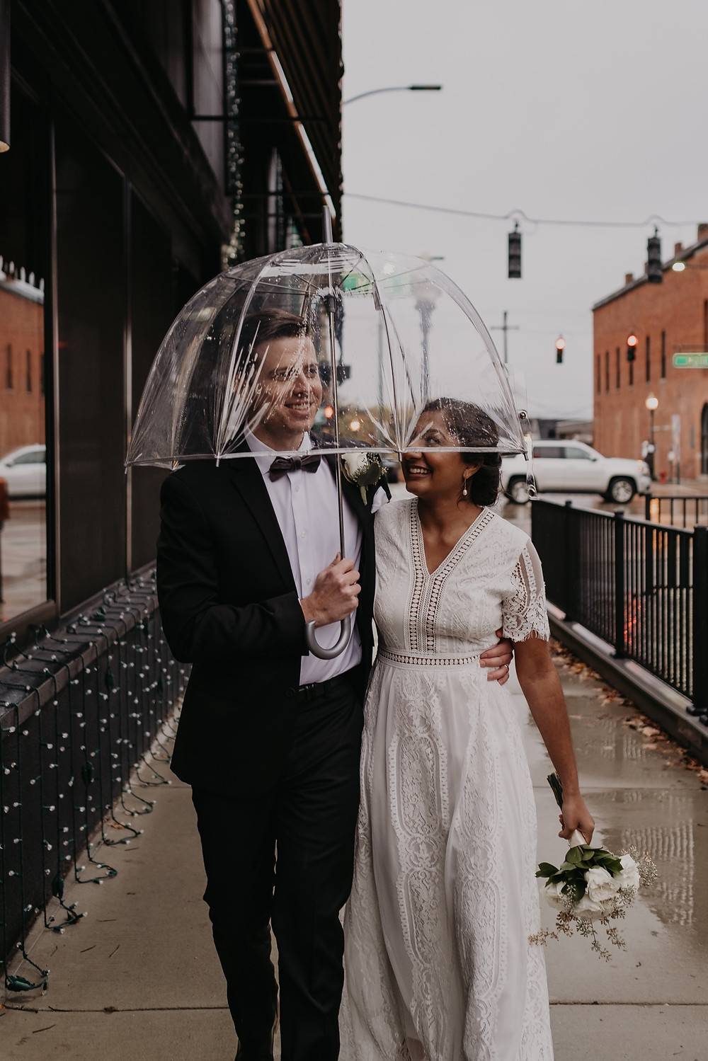 Bride and groom with umbrella on wedding day. Photographed by Nicole Leanne Photography.