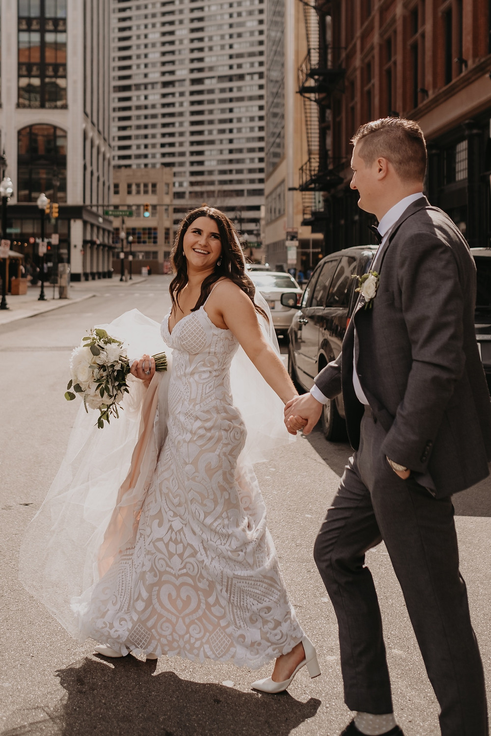 Bride and groom walking in Downtown Detroit. Photographed by Nicole Leanne Photography.