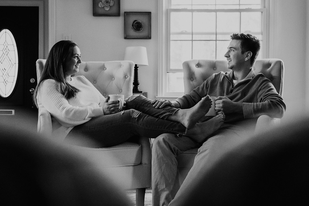 Black and white photo of couple at home in living room. Photographed by Nicole Leanne Photography.