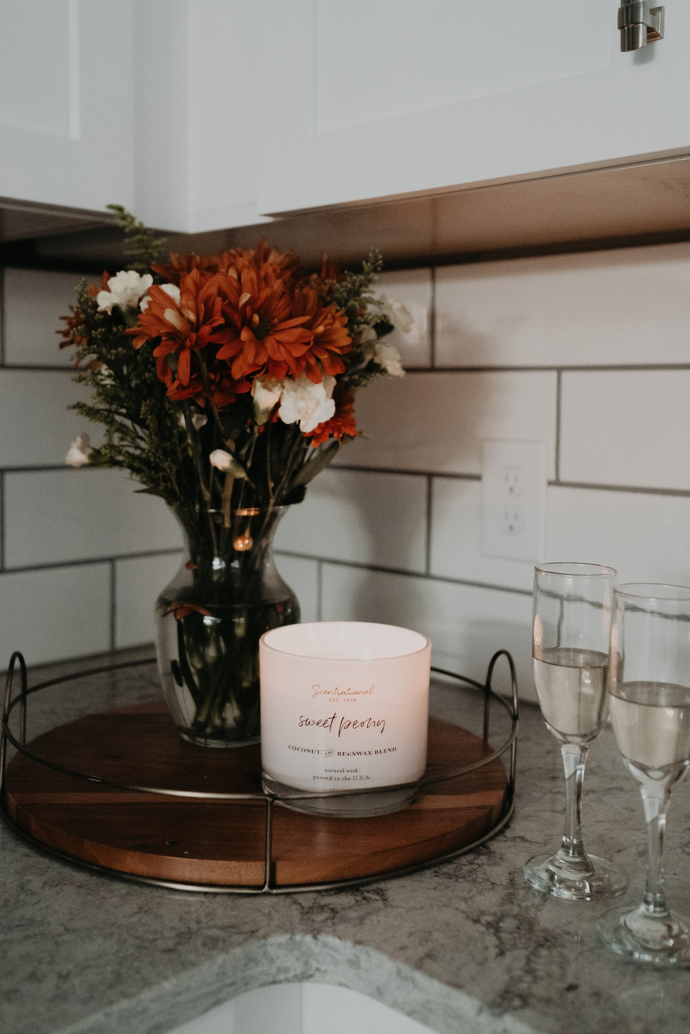 Champagne flutes and flowers at home engagement session. Photographed by Nicole Leanne Photography.