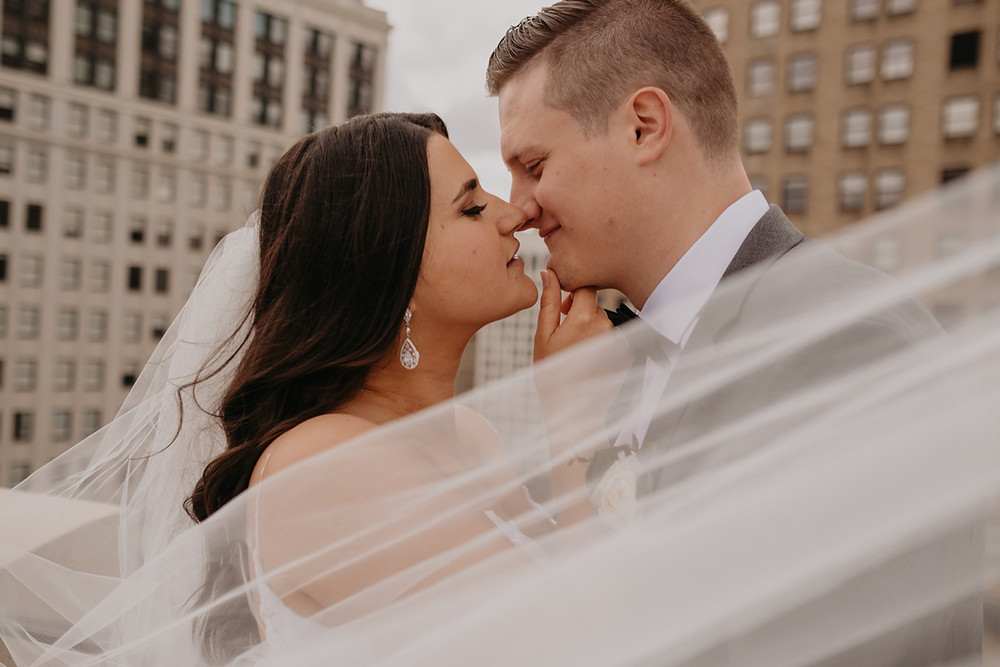 Bride and groom kissing with veil. Photographed by Nicole Leanne Photography.