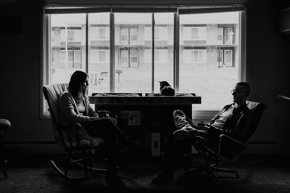 Silhouette of couple and cat at home in black and white. Photographed by Nicole Leanne Photography.