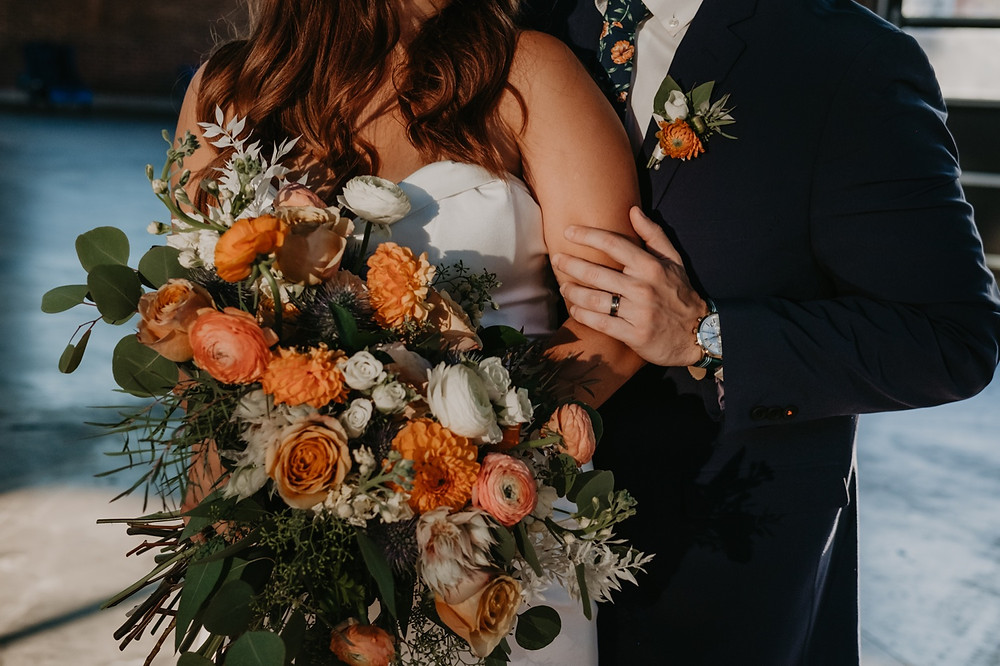 Bride and groom with wedding day floral arrangements photographed by Nicole Leanne Photography