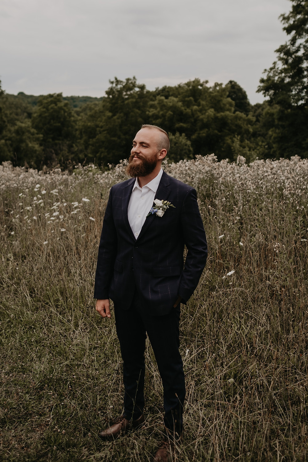 Groom smiling on wedding day in open field in Metro Detroit. Photographed by Nicole Leanne Photography.