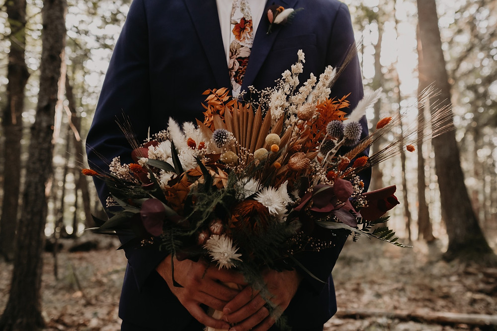 Groom holding dried sustainable wedding bouquet in the woods