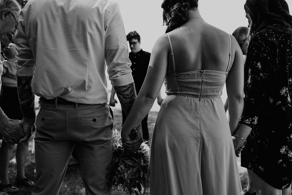 Prayer circle at Metro Detroit park wedding. Photographed by Nicole Leanne Photography.