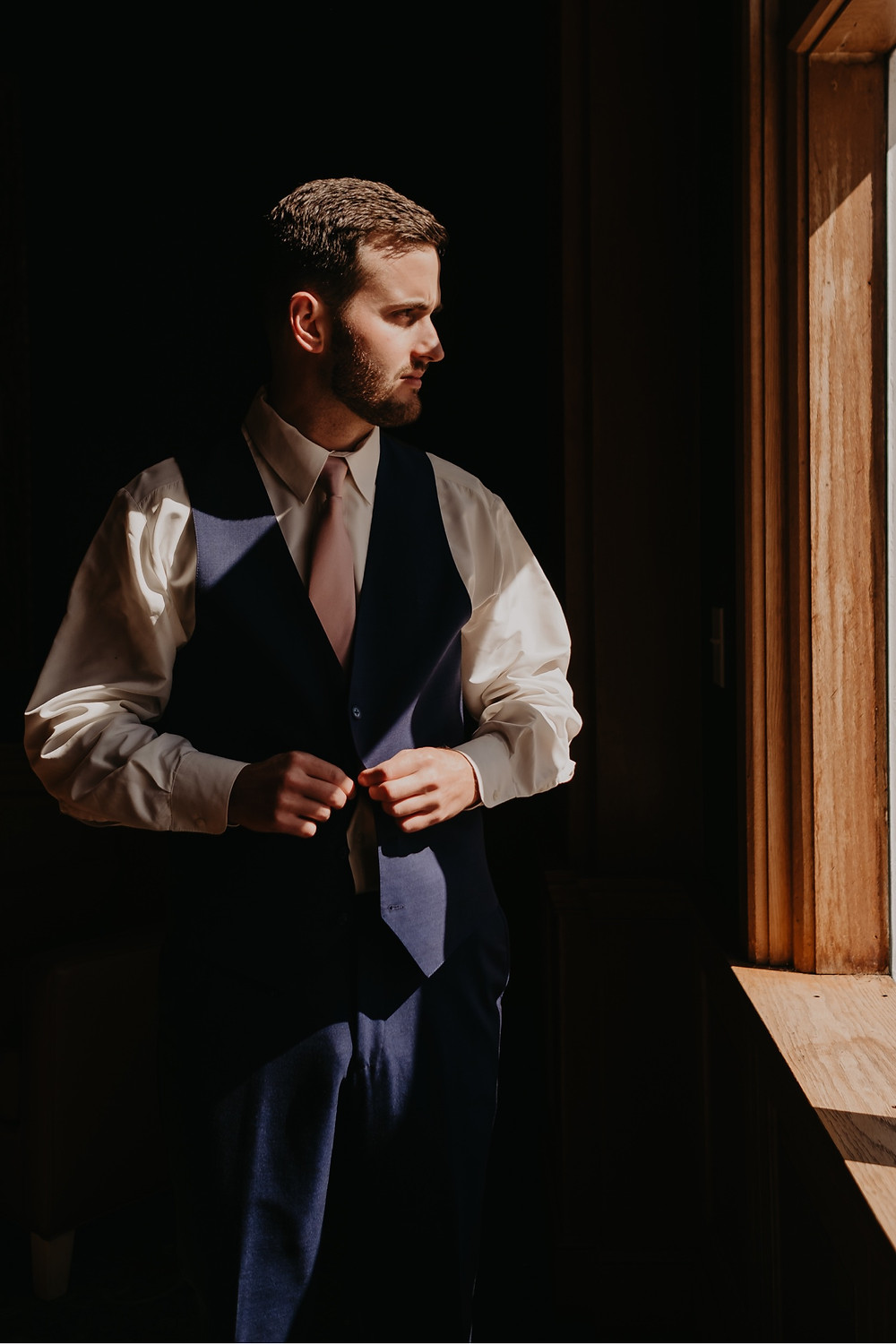 Groom getting dressed in suit for wedding. Photographed by Nicole Leanne Photography.