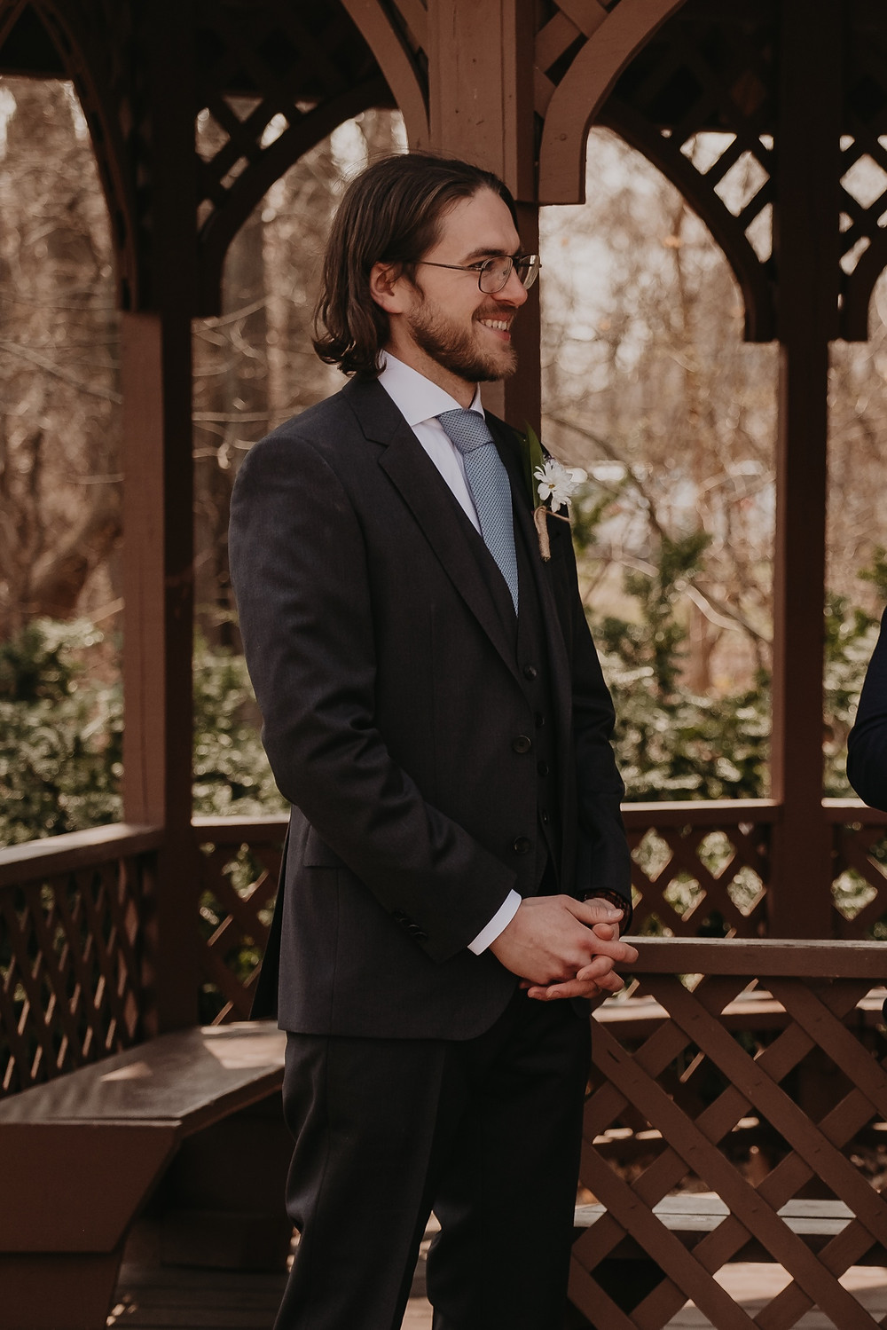 Groom standing at park gazebo on Spring wedding day. Photographed by Nicole Leanne Photography.