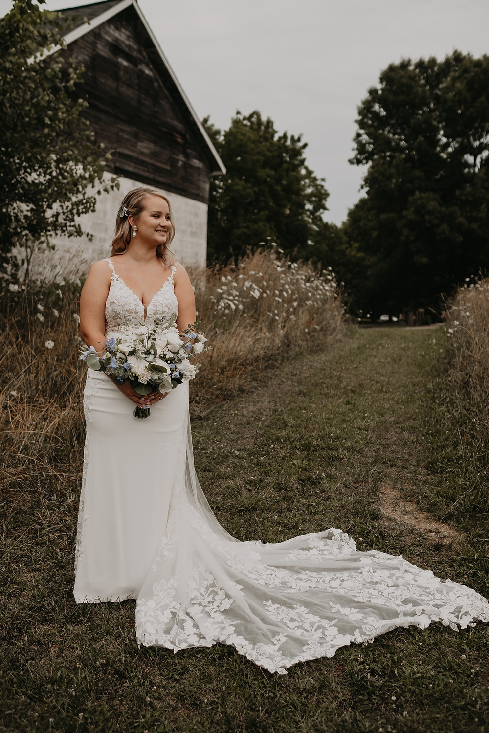 Bride holding wedding bouquet crafted by Love In Bloom at farm