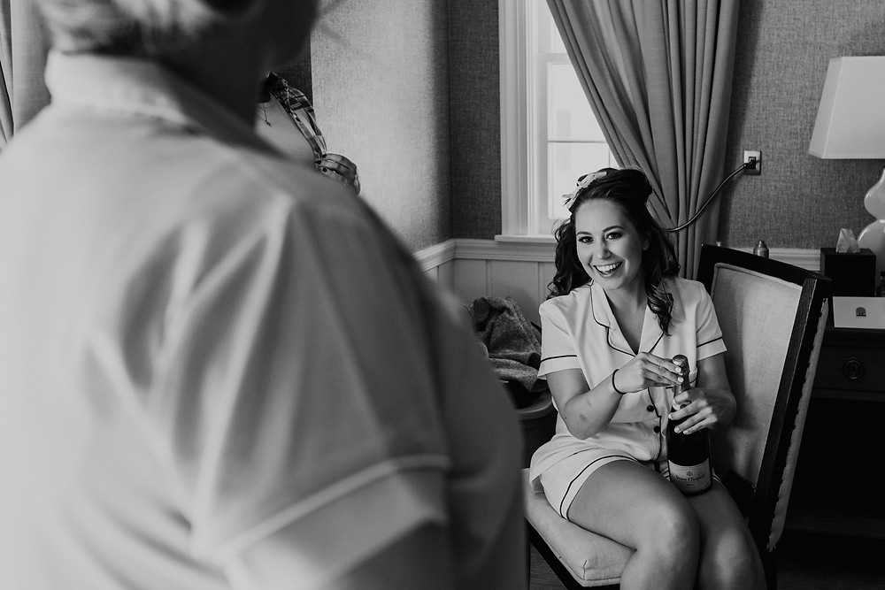 Bride opening champagne on wedding day. Photographed by Nicole Leanne Photography.