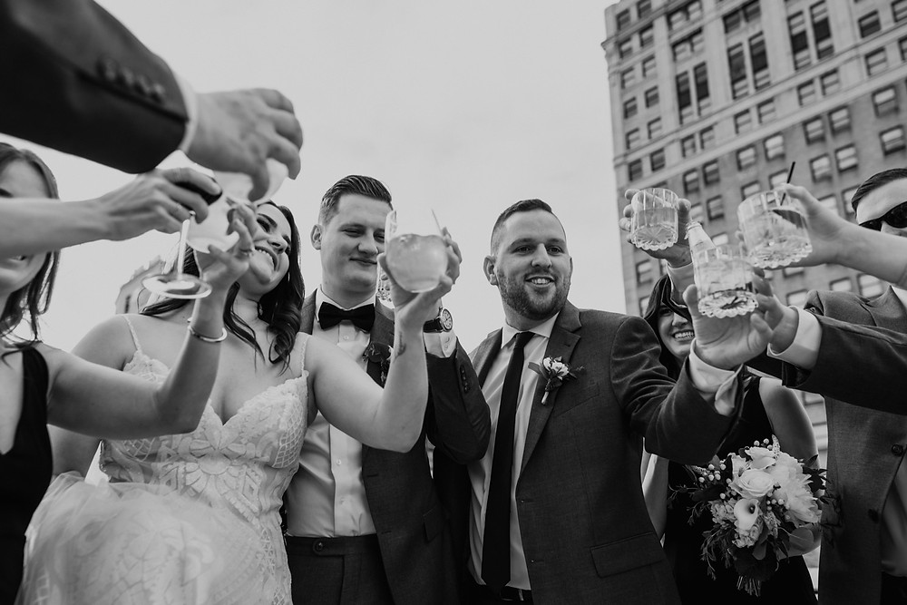 Black and white wedding party wedding photo of champagne toast.