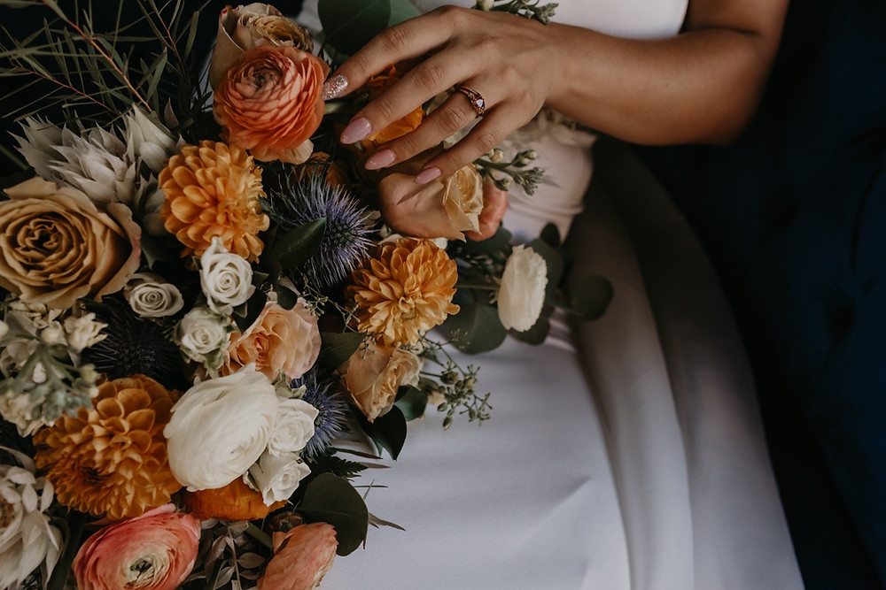 Bride holding wedding bouquet by Copper + Sage Collective