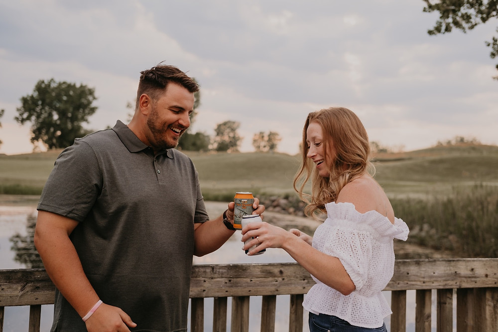 Engaged couple sharing beers at golf course in Metro Detroit. Photographed by Nicole Leanne Photography