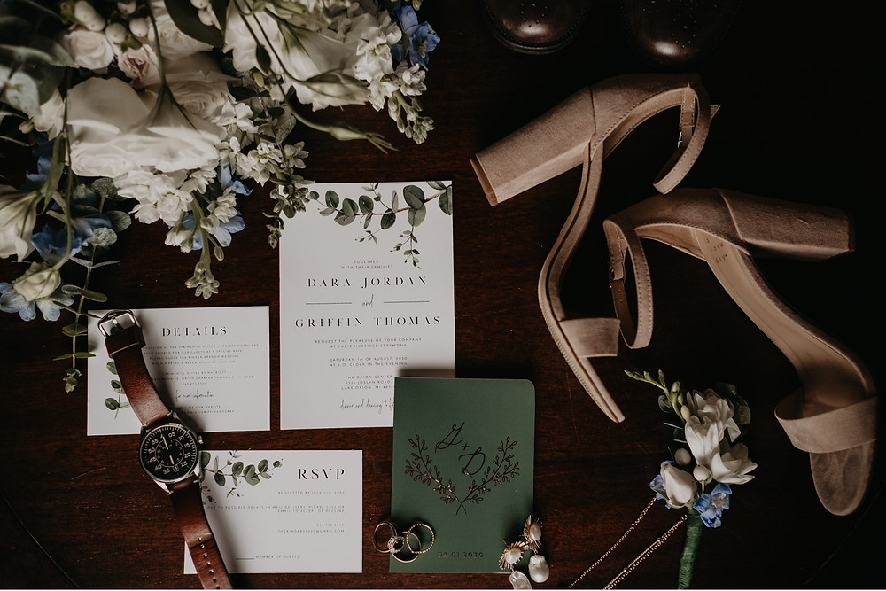 Wedding stationary, florals and accessories laid out on table.