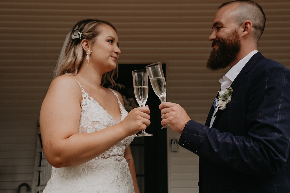 Bride and groom toast with champagne on wedding day. Photographed by Nicole Leanne Photography.