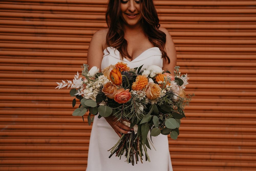 Bride holding fall wedding bouquet. Photographed by Nicole Leanne Photography.