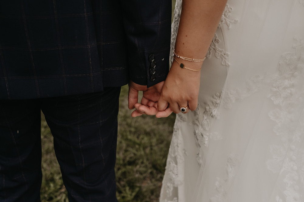 Bride and groom holding hands at wedding. Photographed by Nicole Leanne Photography.