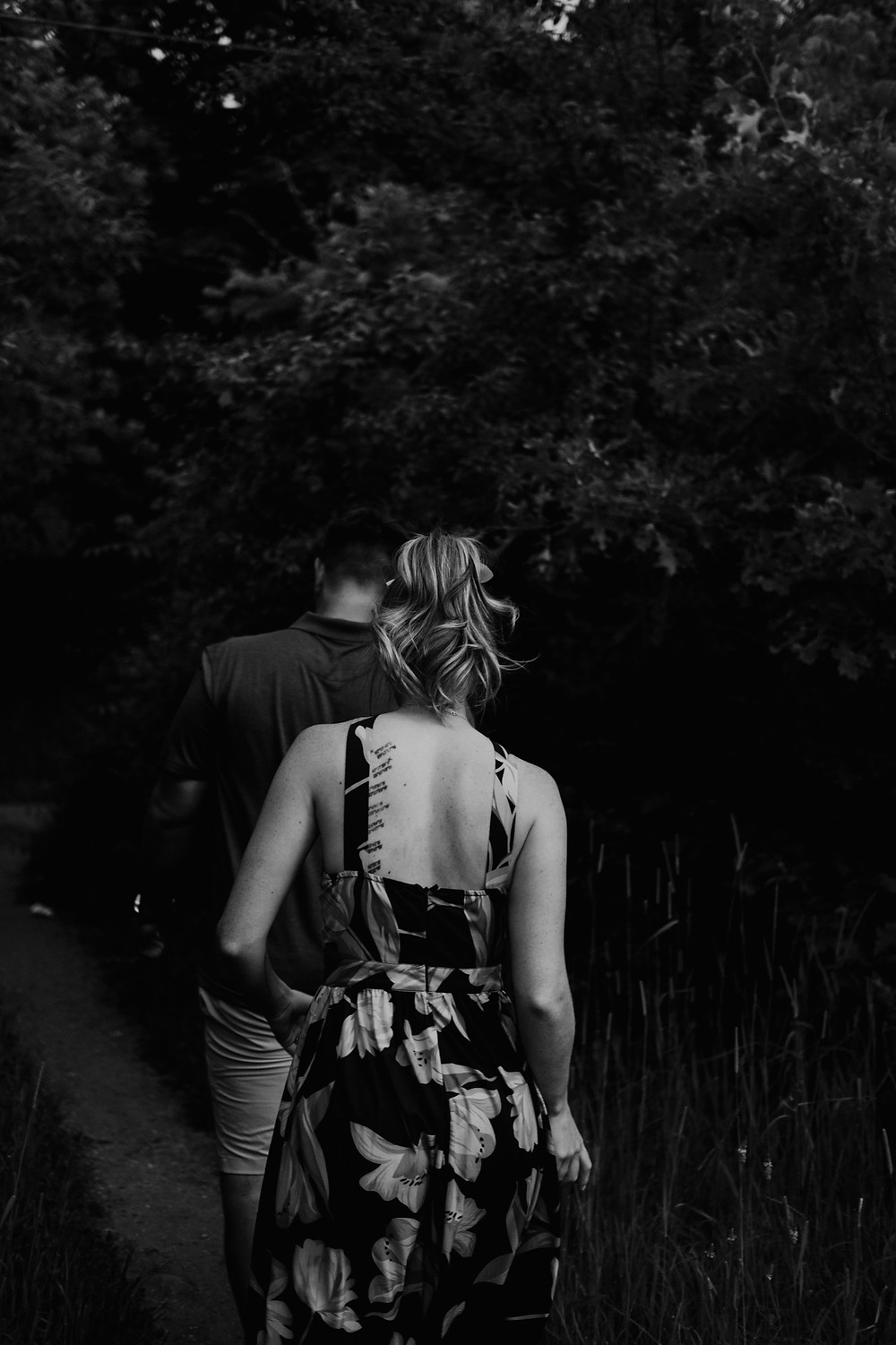 Couple walking down trail at park in Metro Detroit. Photographed by Nicole Leanne Photography
