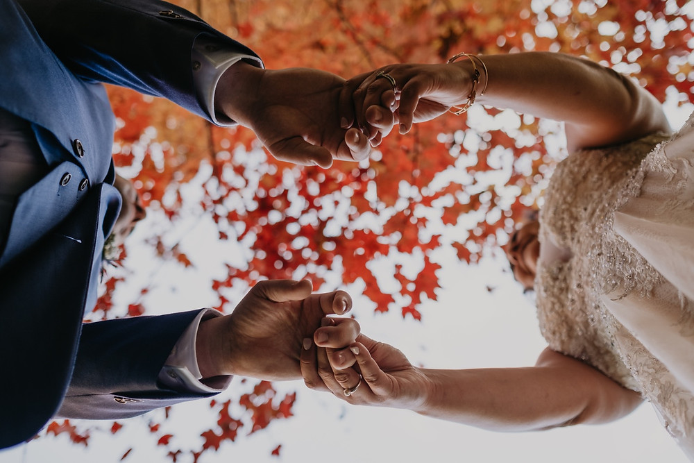 Bride and groom hold hands above camera with fall colors in background