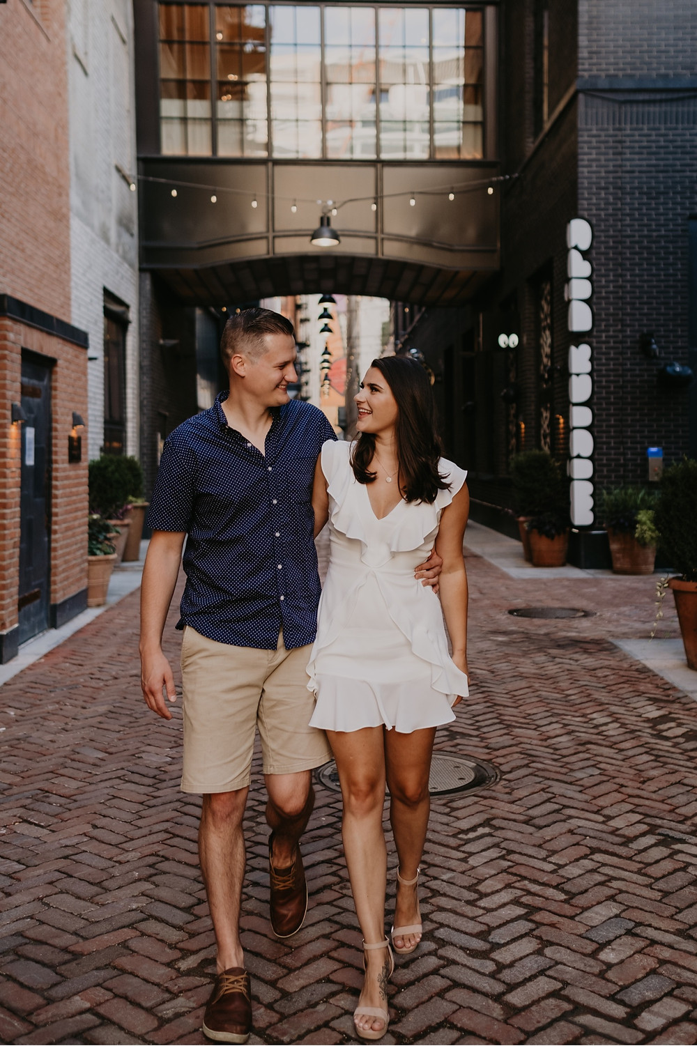 Couple walking down Parkers Alley in Detroit for engagement photos. Photography by Nicole Leanne Photography