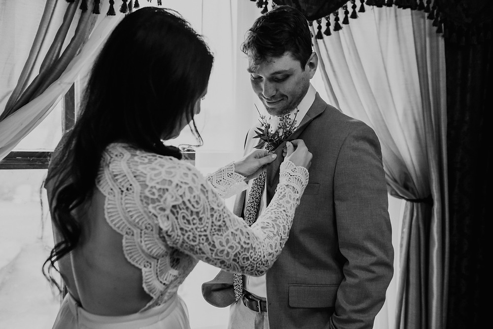 Bride pinning groom's boutonniere on wedding day. Photographed by Metro Detroit Wedding Photographer Nicole Leanne Photography
