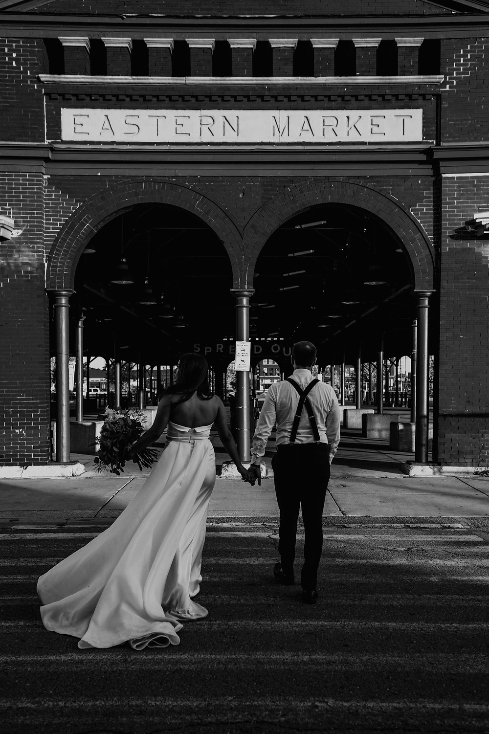 Couple standing outside Eastern Market in Detroit. Photographed by Nicole Leanne Photography.