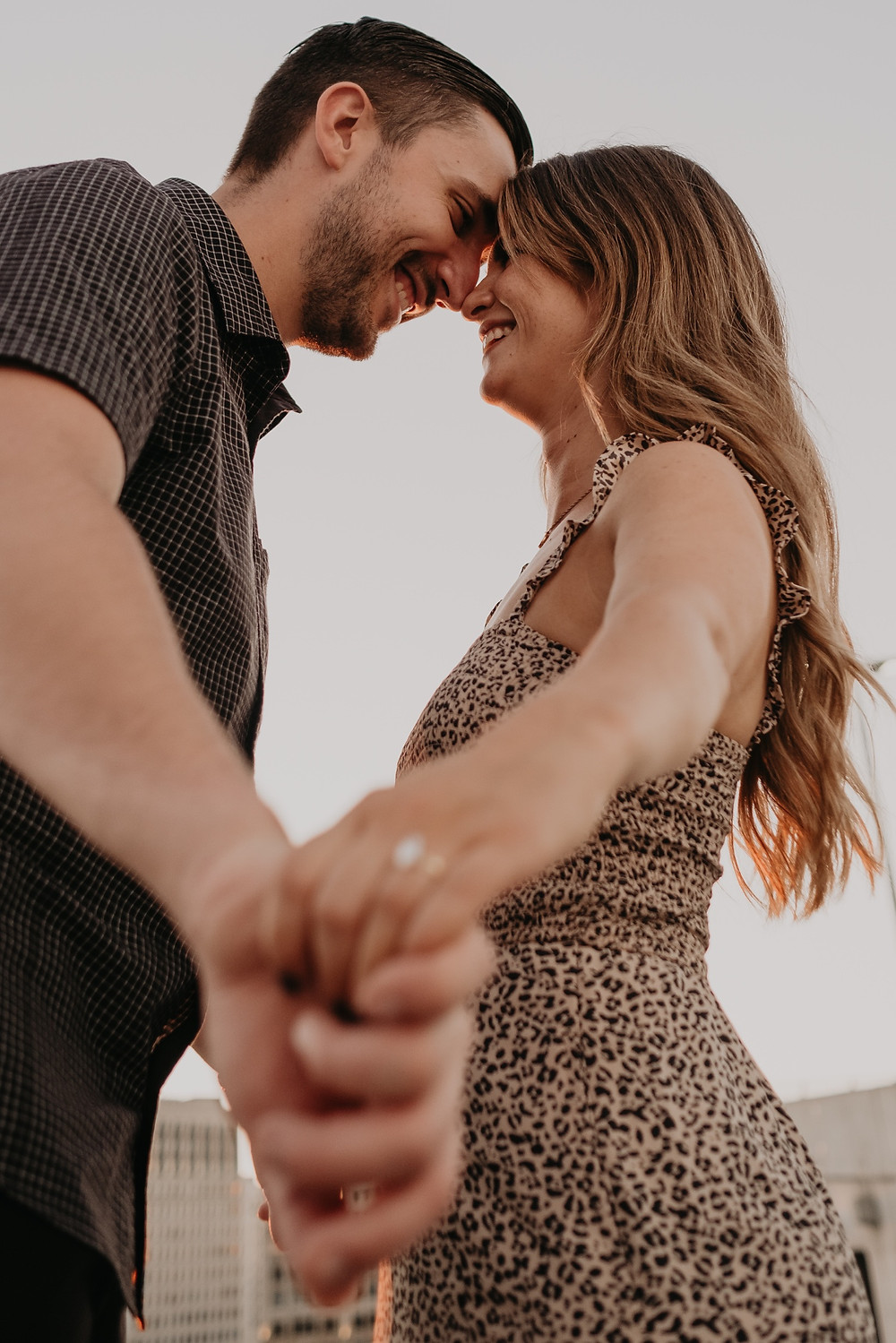 Couple holding hands at sunset on city rooftop. Photographed by Nicole Leanne Photography.